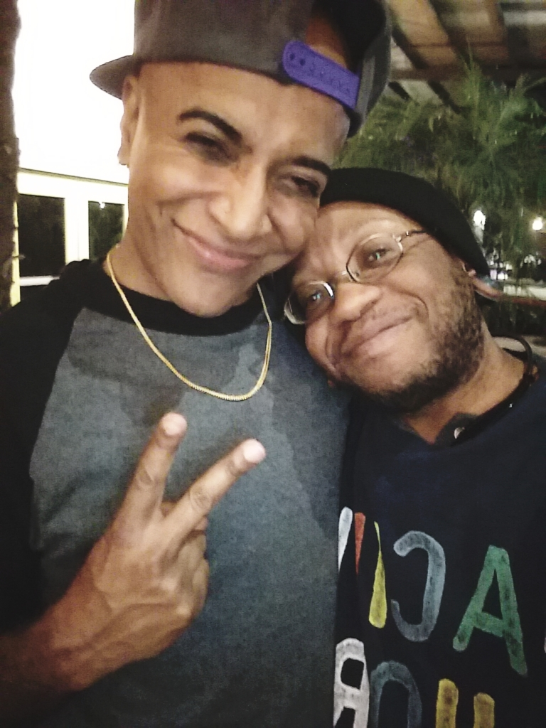 A brown guy wearing a backwards baseball cap, grey/black baseball shirt, a thin gold chain, holding up a peace sign, smiling with his arm around a shorter brown guy wearing a black beanie, glasses, bluetooth headphones around his neck. He is smiling with his head resting on his friend's shoulder.